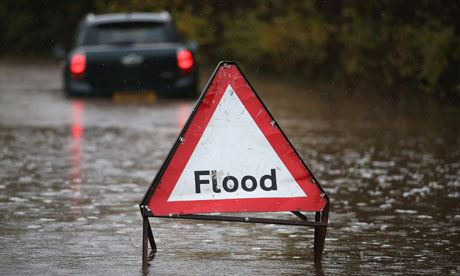 "A sign reads ""Flood"" in a street filled with water"